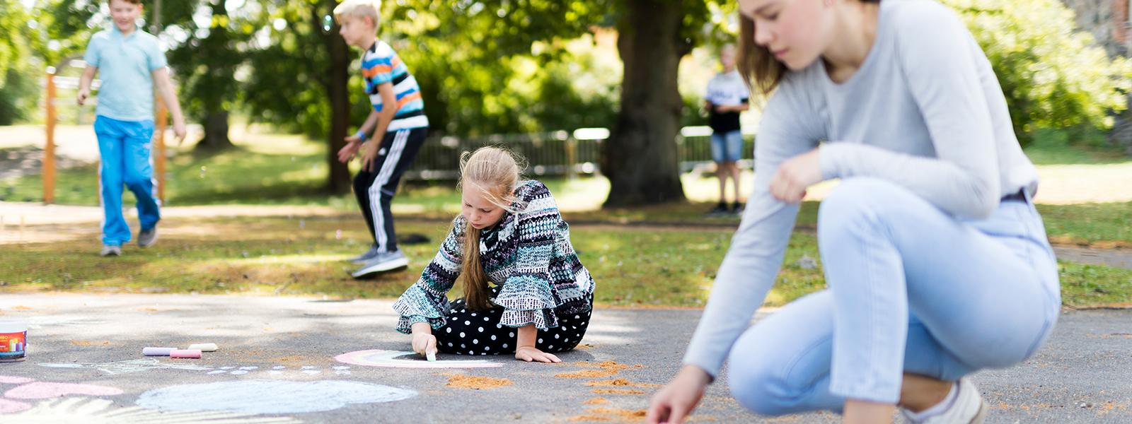 Lapset leikkivät erilaisia leikkejä pihalla