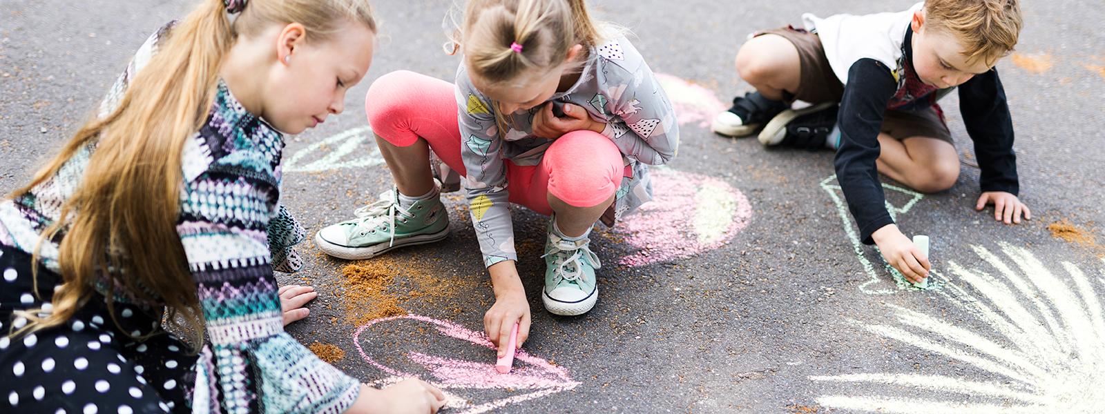 Kaksi tyttöä ja poika piirtävät katuliiduilla