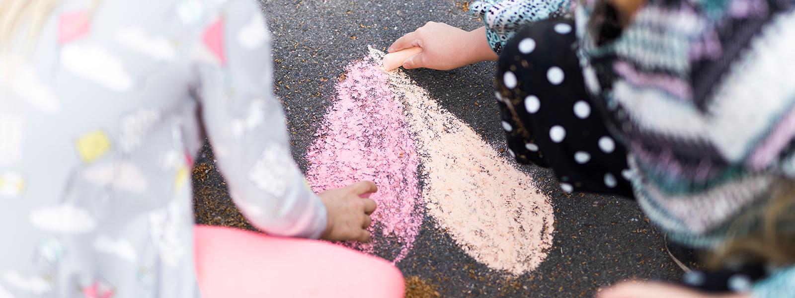 Kaksi lasta piirtää sydäntä katuliiduilla