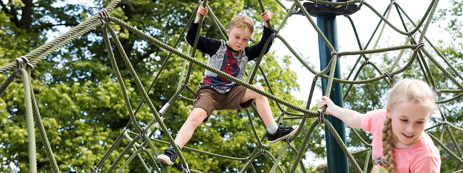 Lapset kiipeilevät kiipeilyverkossa