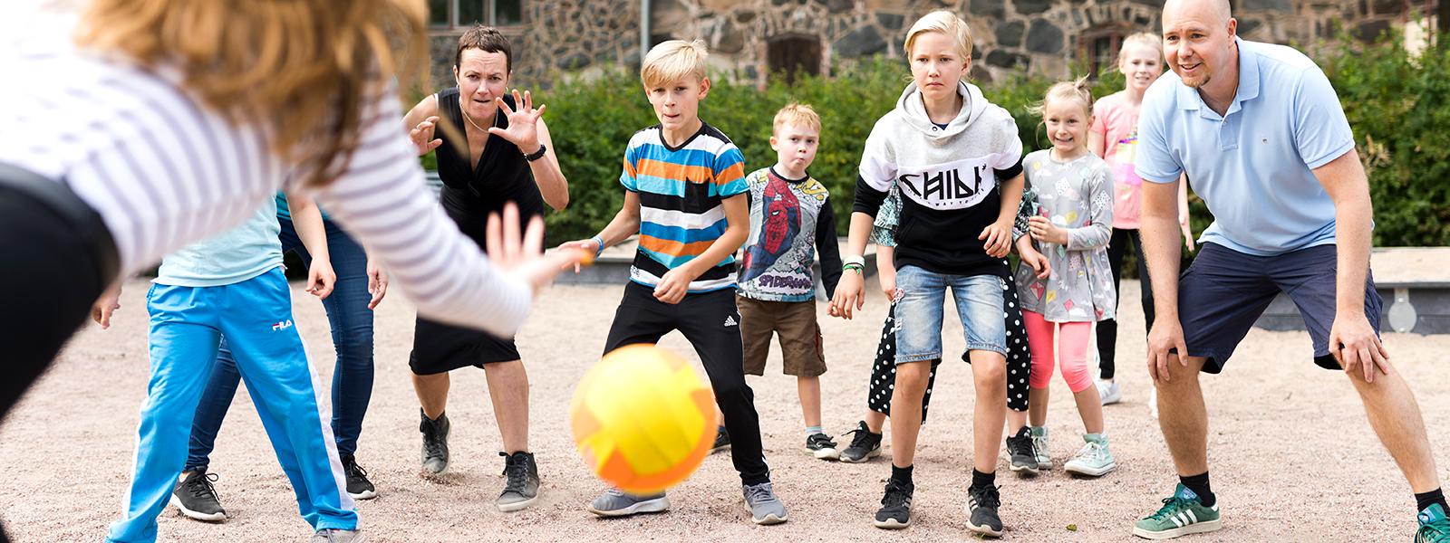 Lapset ja aikuiset pelaavat pallopeliä