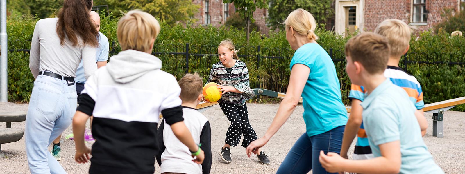 Aikuiset ja lapset pelaavat polttopalloa