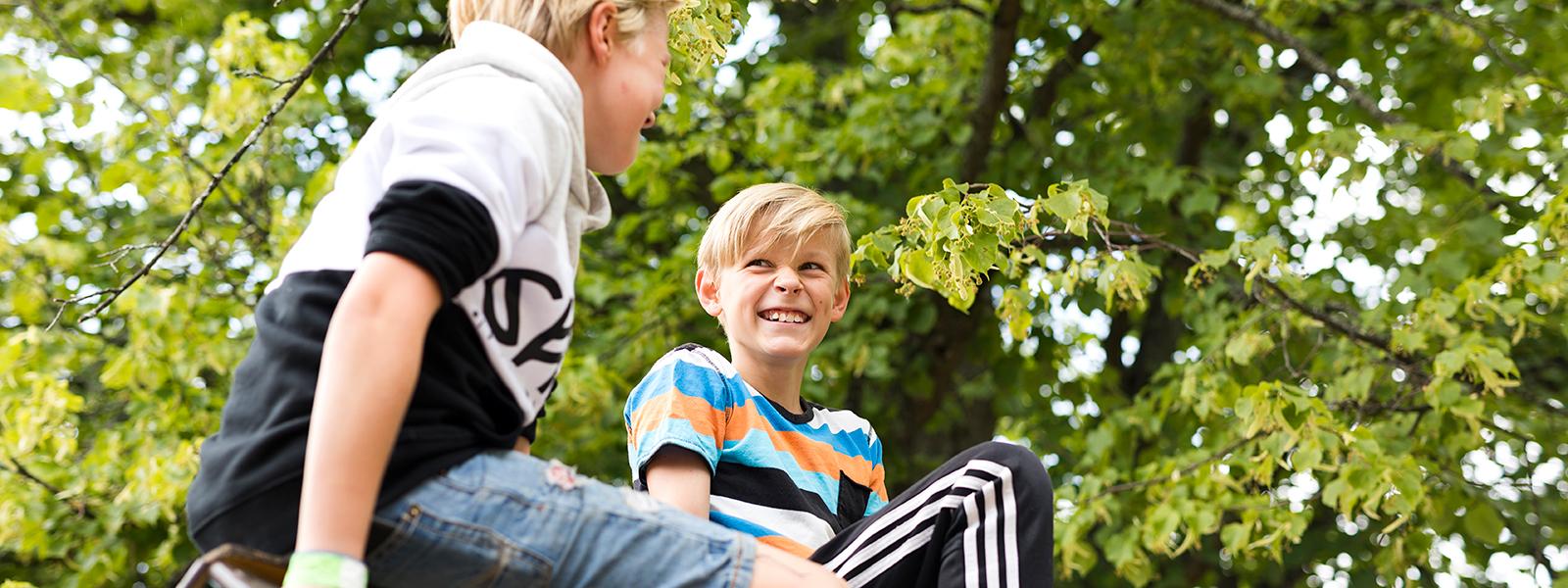 Kaksi poikaa istuu ja nauraa yhdessä