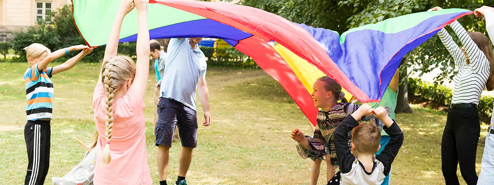 Aikuiset ja lapset kannattelevat leikkivarjoa, tyttö juoksee varjon alta.